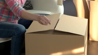 Woman packing cardboard box. Hands using adhesive tape. Best postal services.