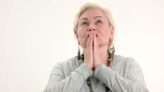 Woman praying on white background. Senior lady with folded hands.