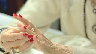 Woman putting on ring with diamond. Well-groomed hands with red manicure of senior woman wearing many golden rings. Beauty and luxury.