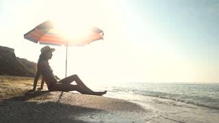 Woman sitting near beach umbrella. Girl, sea and sun. Hot summer on exotic island.