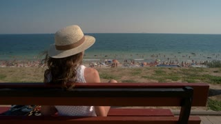 Woman sitting on bench, sea. Lady putting on sunglasses. Brightness of sun.