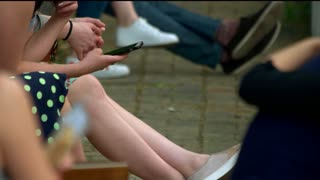 Woman smoking and using smartphone. Close up. Teenagers hanging out.