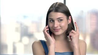 Woman talking on phone and flirting. Young playful girl talking on cell phone with smile, blurred background. Woman receiving compliments by phone.