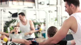 Woman training at gym with personal trainer. Woman training with dumbbells with a help of fitness instructor.