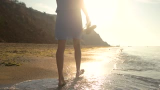 Woman walking on sunny beach. Lady near water.