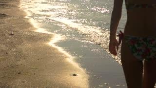 Woman walking on the beach. Young female in bikini. Few steps closer to paradise.
