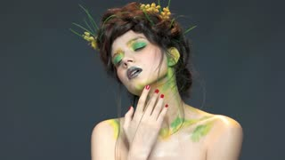 Woman wearing nature themed makeup. Attractive girl touching her face. Building career in beauty industry.