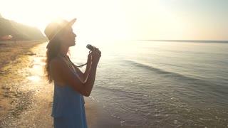 Woman with binoculars on seashore. Lady on the beach, summer. Look beyond the horizon.