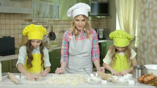 Woman with kids, kitchen. Little girls making pastry. Cooking teacher jobs.