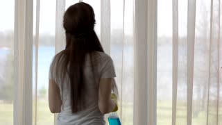 Woman with rag cleans window. Busy girl indoors. Buy cleaning products.