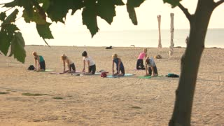 Women doing yoga, beach. Health and fitness tips.