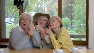 Women in cafe taking selfie. Senior ladies showing thumbs up. Old friends get together.