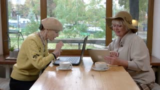Women with tablet and laptop. Senior ladies talking in cafe.
