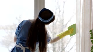 Work of a housemaid. Woman wiping window.