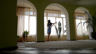 Work of housemaid. Female water spraying a plant.