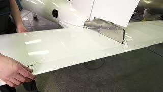 Worker and tail of airplane. White shiny metal. Aircraft maintenance check.