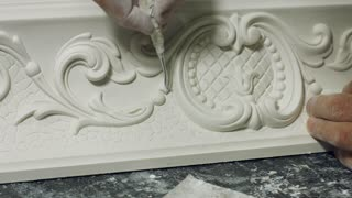 Worker cleaning gypsum ornament close up. Man working with ornament of gypsum construction. Stucco molding concept. Beauty of classical architecture. Restoration of baroque style building.