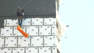 Worker insulating building exterior. Workman hanging on rope.