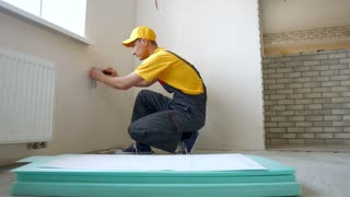 Worker making apartment renovation by project. Builder making a mark on the plan.
