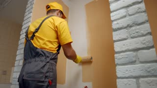 Worker paints the wall roller. House painter paints the wall in brown.