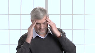 Worker with headache massaging his head to reduce pain. Mature man syffering from head pain indoor against bright windows background.