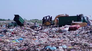 Workers at the city dump. Trucks unload garbage to the dump. Recycling of of municipal waste. Recycle Garbage machines on a landfill.
