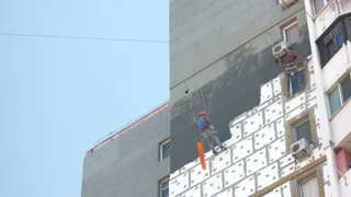 Workers insulating building exterior. Apartment block and sky. Risky job on heights.