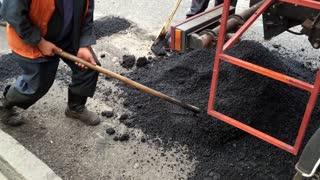 Workers with shovels repairing asphalt. Men repair damaged road. Machine that helps traffic workers. Asphalt unloaded from truck.