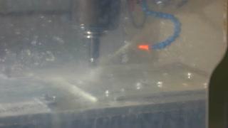 Working cnc machine. Steel and water splashes.