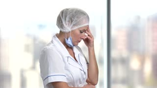 Worried and tired female doctor. Upset mature female doctor holding hand near head in bright windows background.