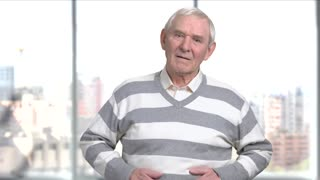 Worried elderly man with stomach ache. Senior man with indigestion, constipation or colon, blurred background. Unhealthy food eating and abdominal problems.