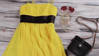 Yellow dress and black purse. Lady's bracelet set and handbag. Seasonal sale with huge discounts. Special offer in local boutique.