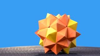 Yellow origami ball on blue background. Kusudama figure on colorful background. Art of folding paper.