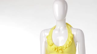 Yellow top on female mannequin. Yellow top with denim skirt. Bright summer top with bijouterie. Teenage girl's outfit on display.