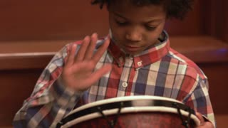 Young afro drummer on stairs. Friendly afro child with drum. Playing djembe like a pro. Free Christmas concert.