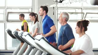 Young and elderly people running on treadmill. Young handsome man runs on treadmill and looking at camera. Workout at modern fitness club.