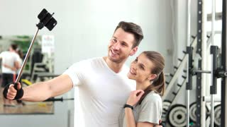 Young athletic couple taking selfie at gym. Young man and woman taking a photo with selfie stick at fitness center. People, sport and technology.