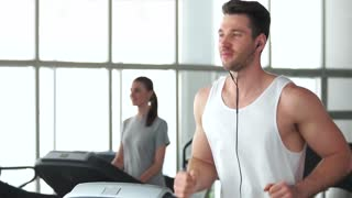 Young athletic man running on treadmill. Handsome muscular guy working out at gym. Always be in fit.