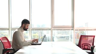 Young bearded man working as freelancer on laptop. Man working on laptop in office with windows background.