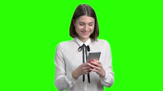 Young brunette girl chatting on smarphopne. Portrait of beautiful girl typing on device. Green screen hromakey background for keying.