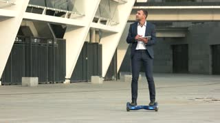 Young businessman on hoverboard. Man holding tablet outdoors. Era of success.
