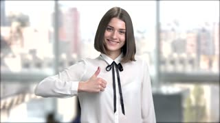 Young charming lady on blurred background. Happy smiling young brunette woman showing two thumbs up. Sign of agreement.