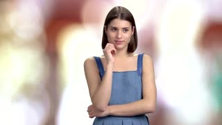 Young cheerful lady is thinking. Beautiful girl with short hair having an idea, blurred background.