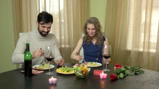Young couple eating. Food and wine on table. What to order in restaurant.