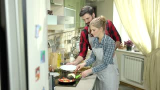 Young couple preparing food. Plate with fried eggs. Breakfast for two.