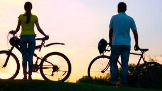 Young cyclists at beautiful sunset. Group of young people with bicycles at amazing sunset. Enjoying the nature.