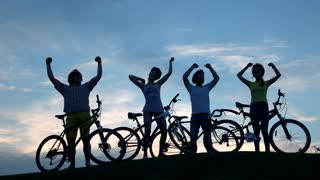 Young dancing cyclists at sunset sky. Group of young cheerful friends having rest outdoors. Happy people dancing at sunset.