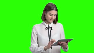 Young female speaker on business conference. Woman with tablet talking and explaining. Green screen hromakey background for keying.