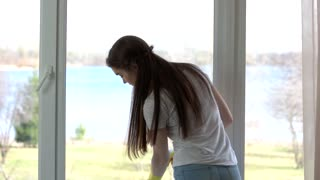 Young female wiping window. Girl working indoors. Best glass cleaner.