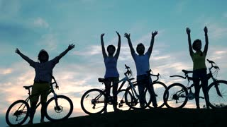 Young friends with bicycles on sky background. Group of young people with bikes waving with hands at beautiful sunset. The best rest ever.